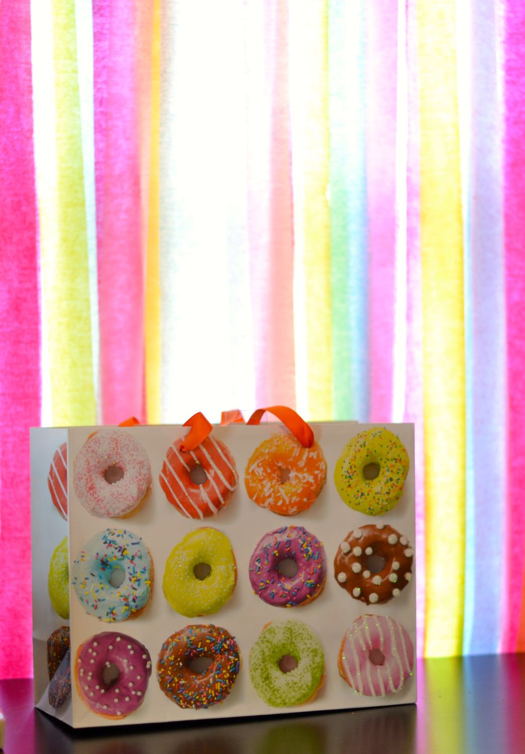sprinkled donut gift bag and rainbow backdrop for a sprinkle birthday theme party // lovelyluckylife.com