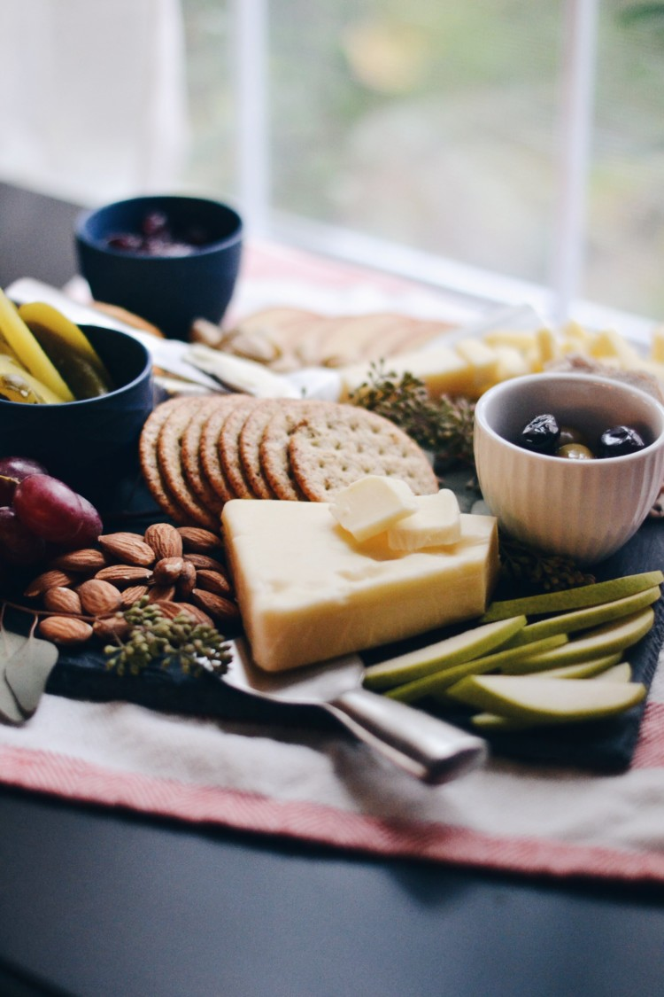 this cheese platter is the perfect mix of cheese, protein, olives, pickles, almonds, and crackers and SO pretty for an appetizer