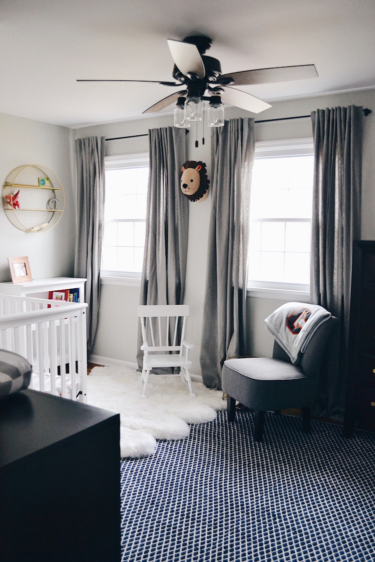 boy room ideas for a toddler - love this neutral room decor with a faux fur rug, a navy rug, grey curtains, and a white crib