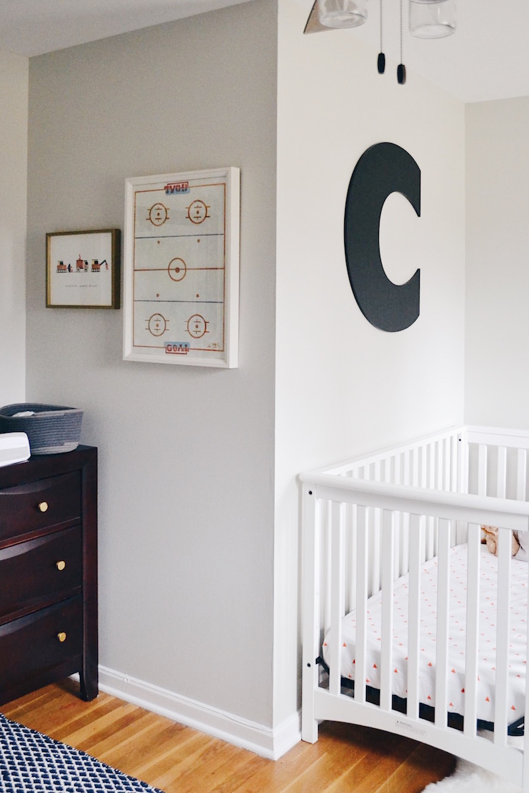 boy room decor - neutral boy room with grey walls and a white crib and dark wood furniture