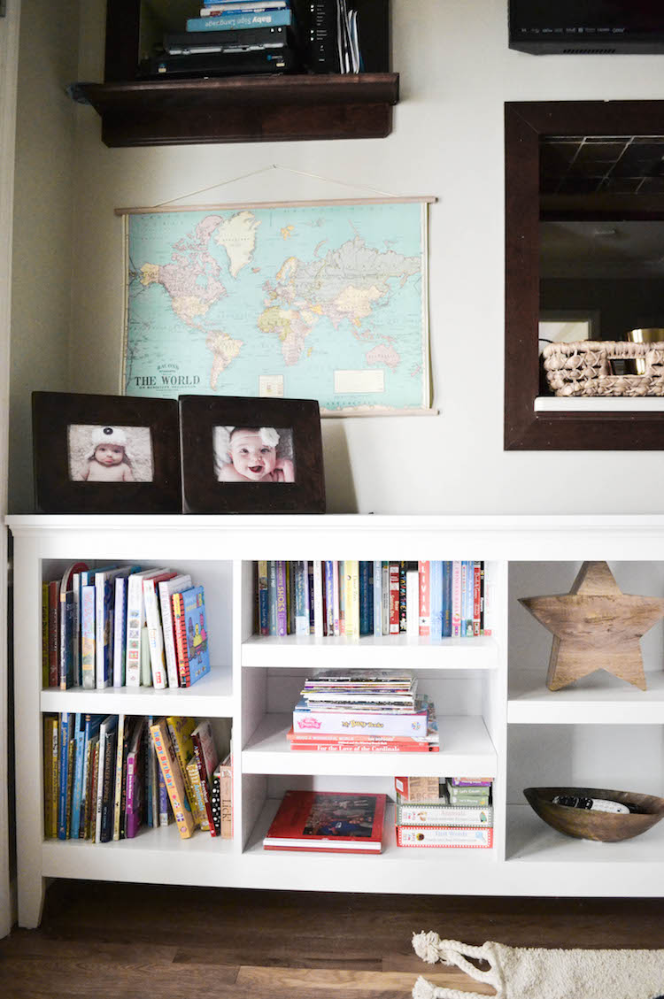 "our playroom den reveal - a shared space for the whole family. love this playroom design that doesn't scream ""toys!"". toy storage tips & tricks. love this white bookshelf that holds kids books + a fun world map print on the wall"