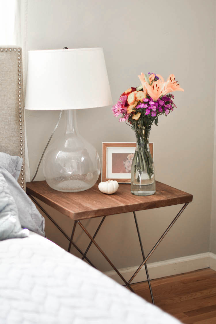 love these fall flowers and a mini white pumpkin on this wood side table as a nightstand for fall decor