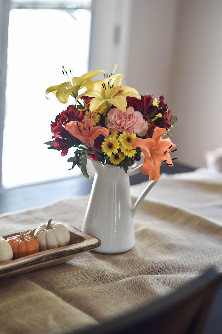 fall flowers in a white pitcher + cute little mini pumpkins on a burlap runner - easy, classic, fresh fall decor for the kitchen table