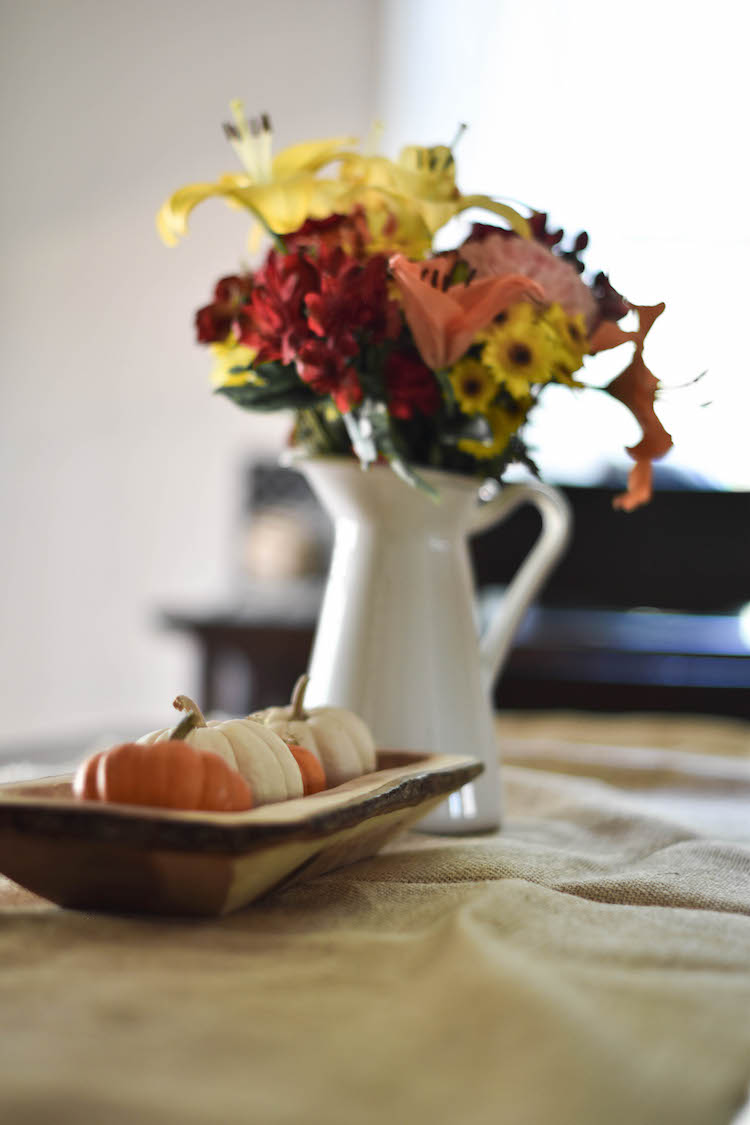mix orange and white mini pumpkins on top of a burlap runner plus fall blooms in a rustic pitcher