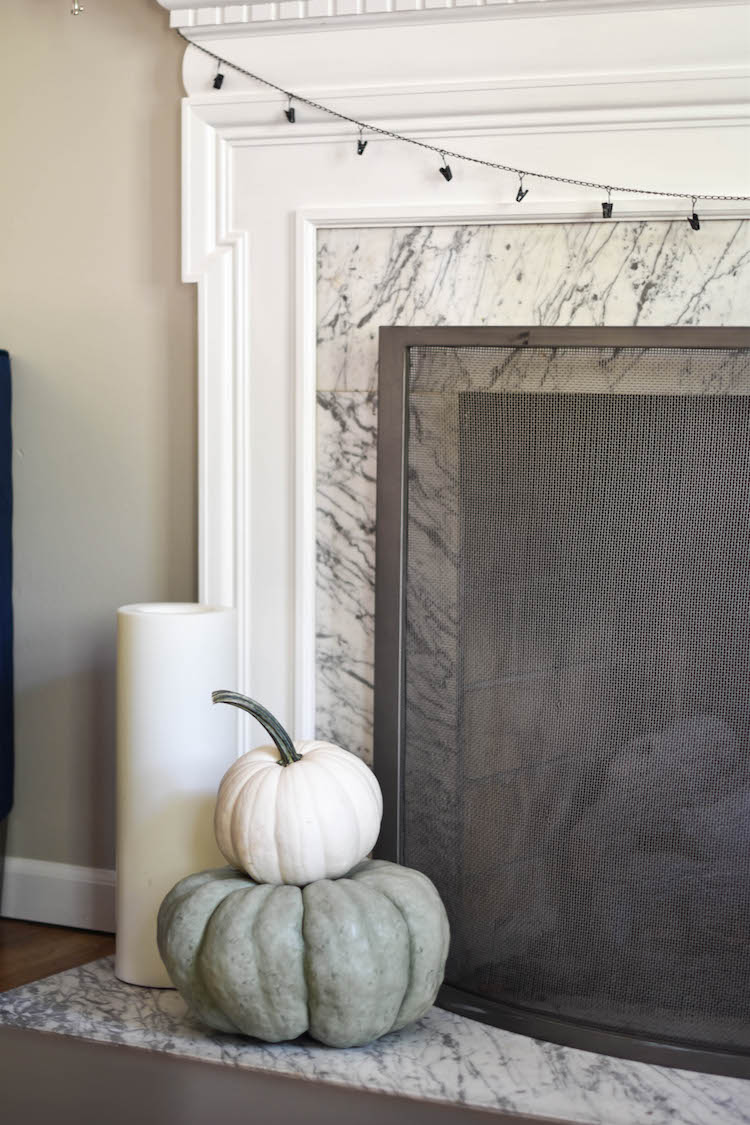 stacked white and green pumpkins are THE BEST fall decor - pumpkins in front of the fireplace