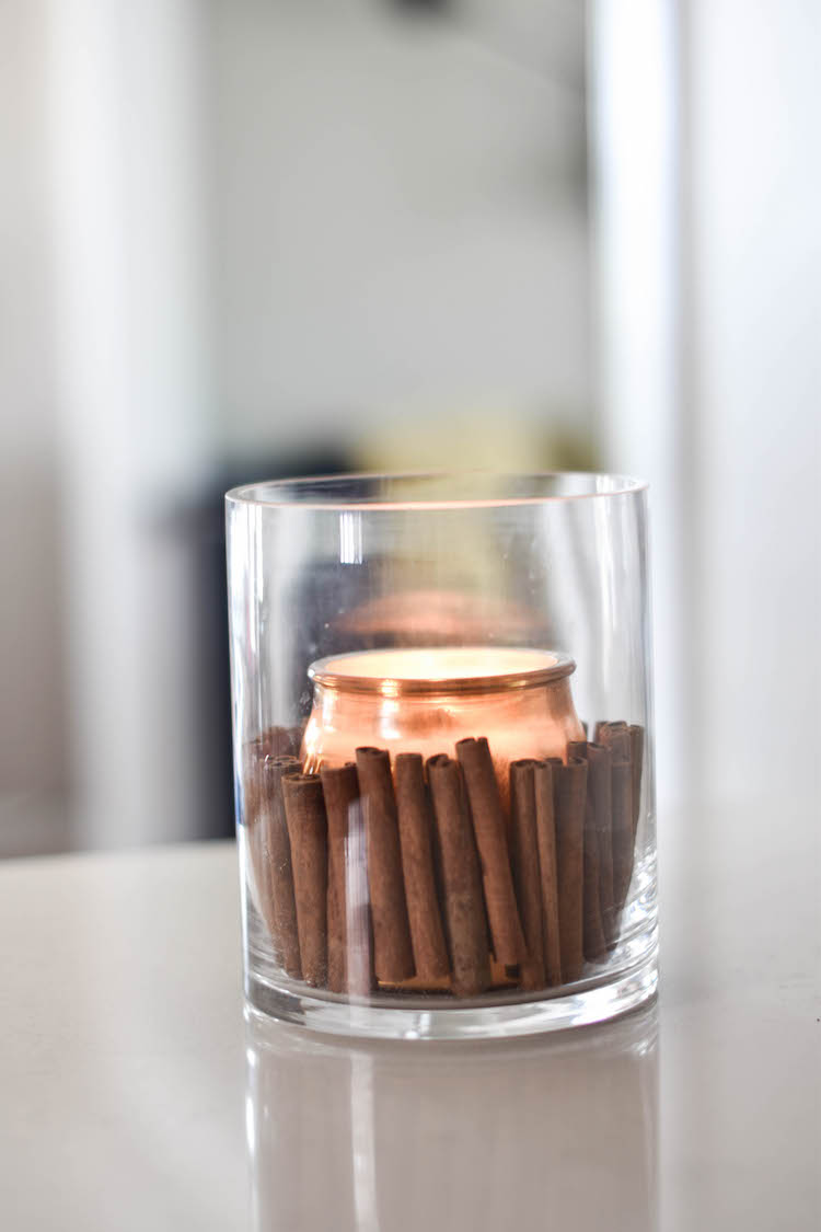 the easiest fall centerpiece EVER - cinnamon sticks in a hurricane jar with a candle. smells SO good!