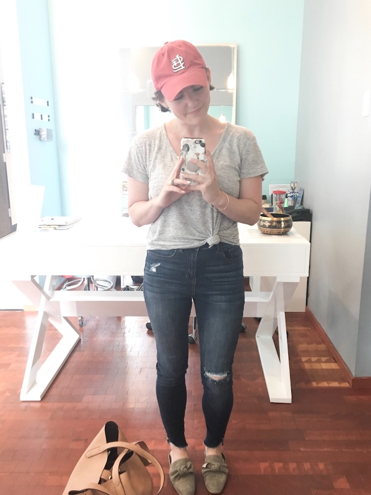 easy everyday mom outfit- knotted tee, ripped skinny jeans, baseball hat and super comfy slide mules