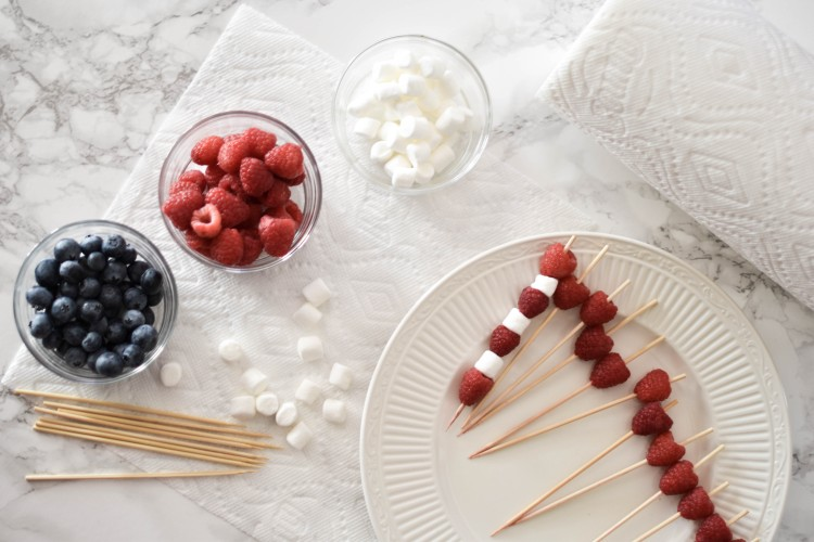 the cute little fruit skewers are perfect for a Fourth of July Party or America themed party. use marshmallows, blueberries and raspberries on skewers to make an adorable little edible American flag