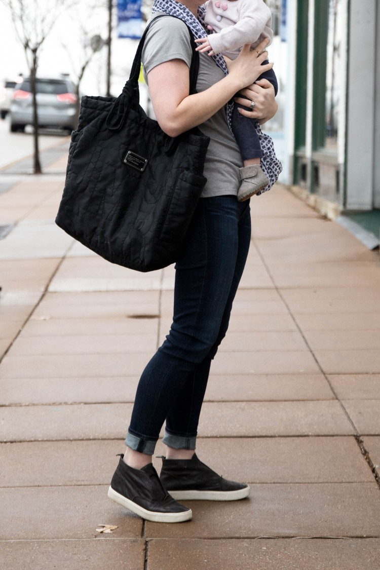 the perfect outfit for stay at home moms - skinny jeans, black sneakers, a comfy tee and a black diaper bag