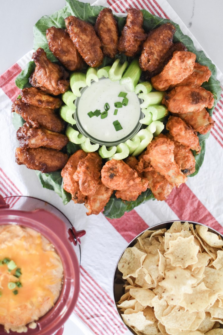 buffalo wings and buffalo dip - the ultimate combo! love this display for buffalo wings with a cup of ranch and celery right in the middle