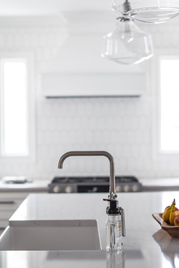 a white kitchen with glass schoolhouse pendants and a modern polished nickel faucet
