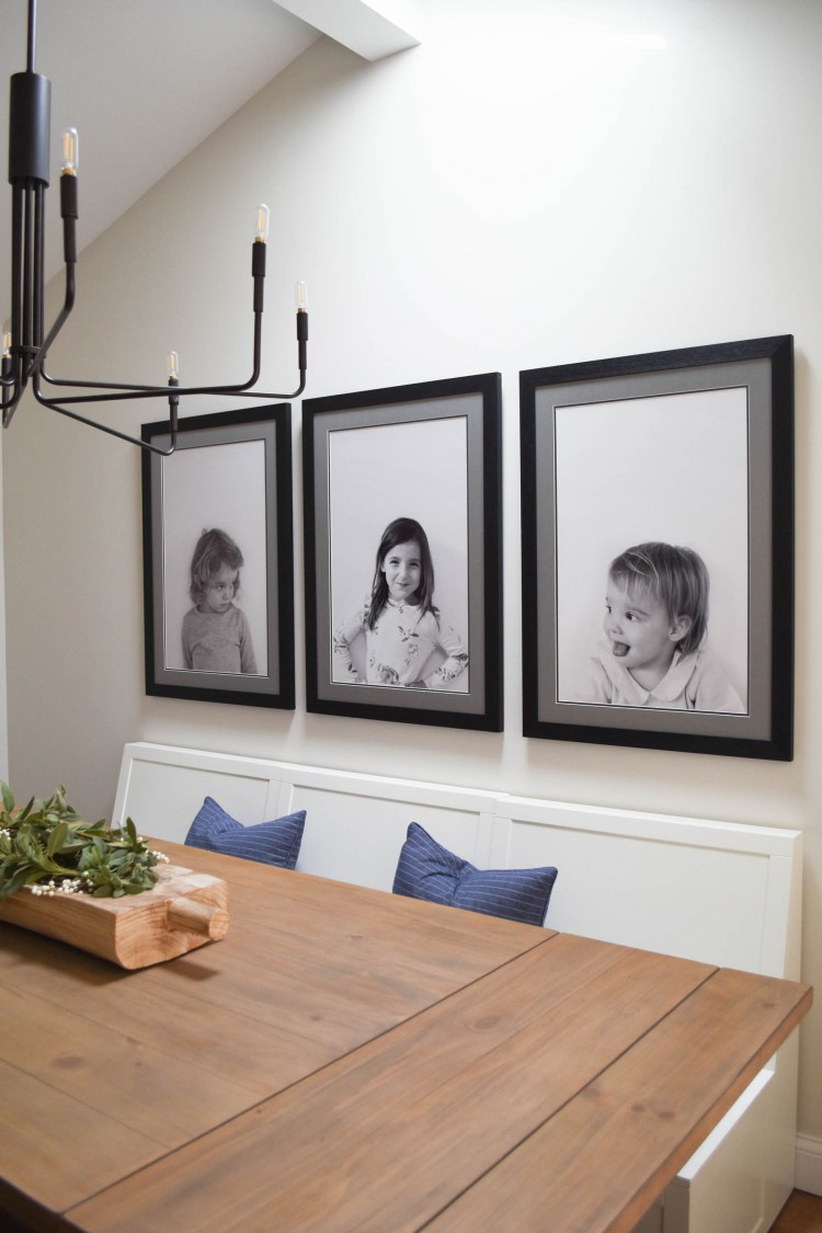 perfect family dining room - big prints of the kids, great black chandelier, and a crisp white banquette bench for seating