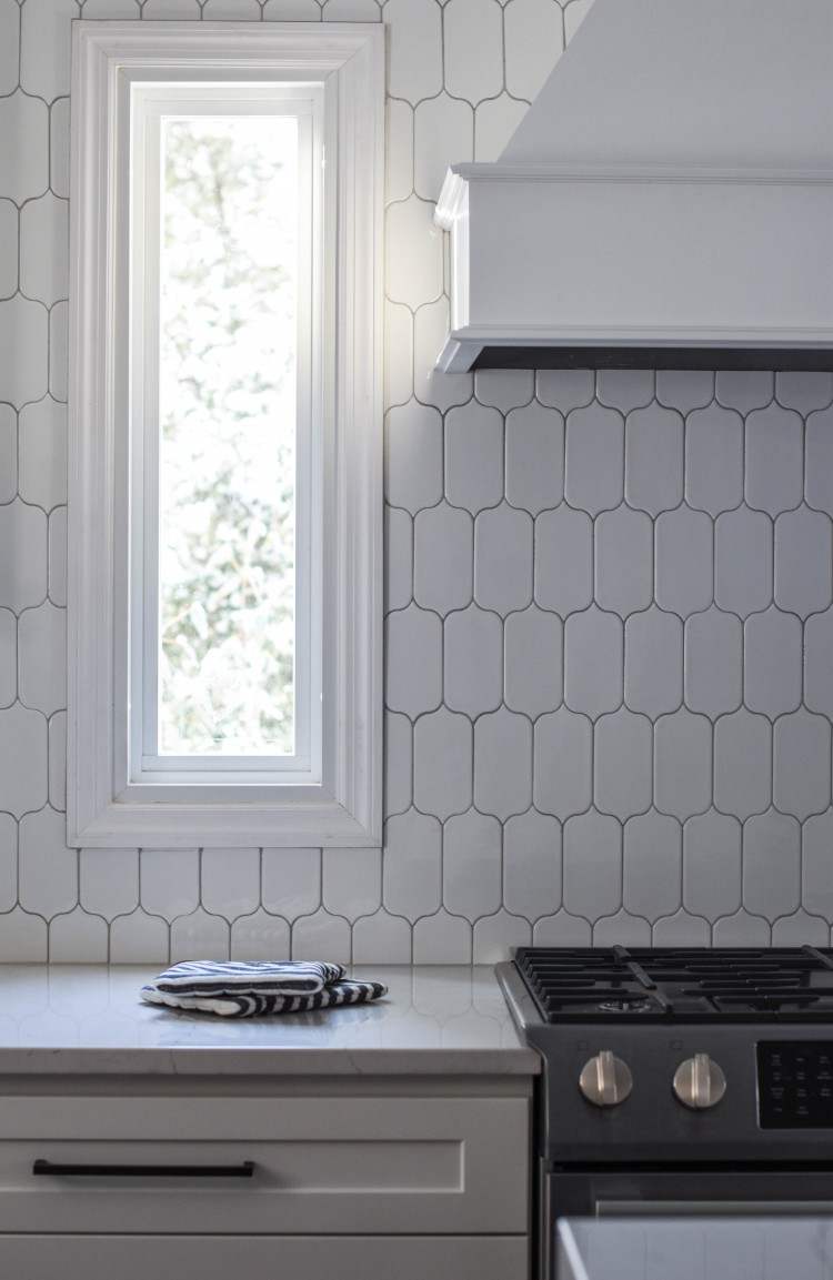 white lantern tile backsplash with a white oven hood - slightly feminine and white yet interesting