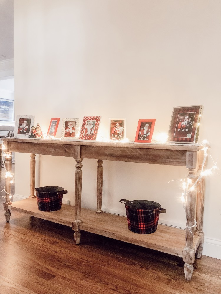 love this santa photo display - put Santa pictures in white and red frames every year and display them on a console table - easy way to display pics of Santa with kids! // How to Display Santa Pictures