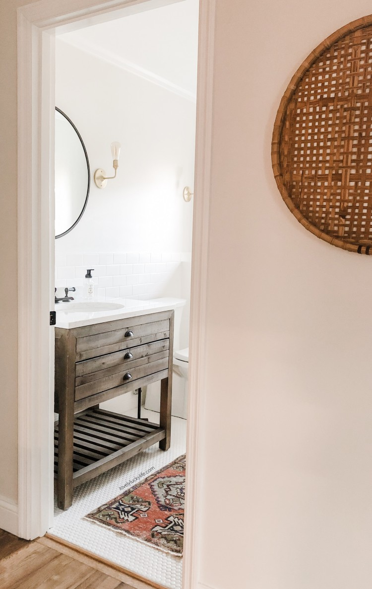 love this half bath design - penny tiles with a skinny Persian rug and a rustic vanity