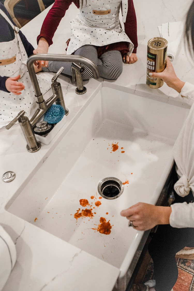 dirty farmhouse sink with pasta stains