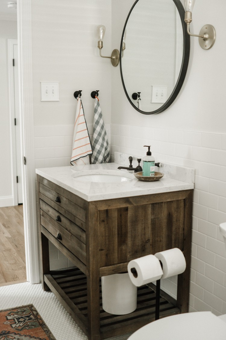 love the large round mirror for the bathroom and the industrial sconces for a farmhouse-vibe in the half bath
