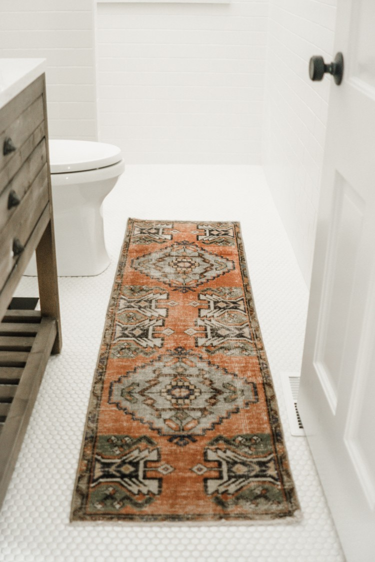 white penny tile floors + classic white subway tile + a pop of color turkish rug - love it for a classic bathroom!
