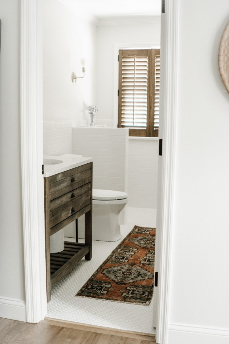 a white half bathroom with a Turkish runner - love the white on white