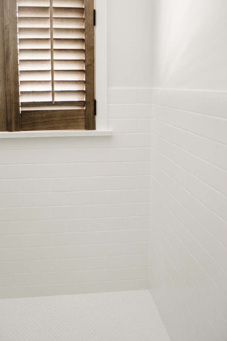 if you've ever thought about white-on-white tile, it's bright, clean and classic! white subway tile with white grout with white penny tile on the floor