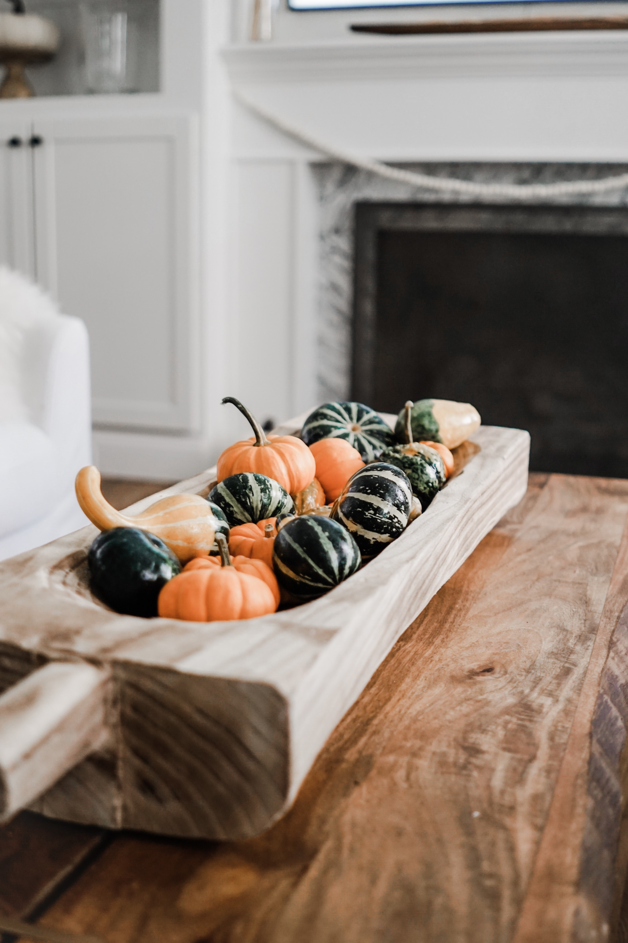 fall decor inspiration - wood basket filled with fresh gourds and mini pumpkins // fall living room decor idea