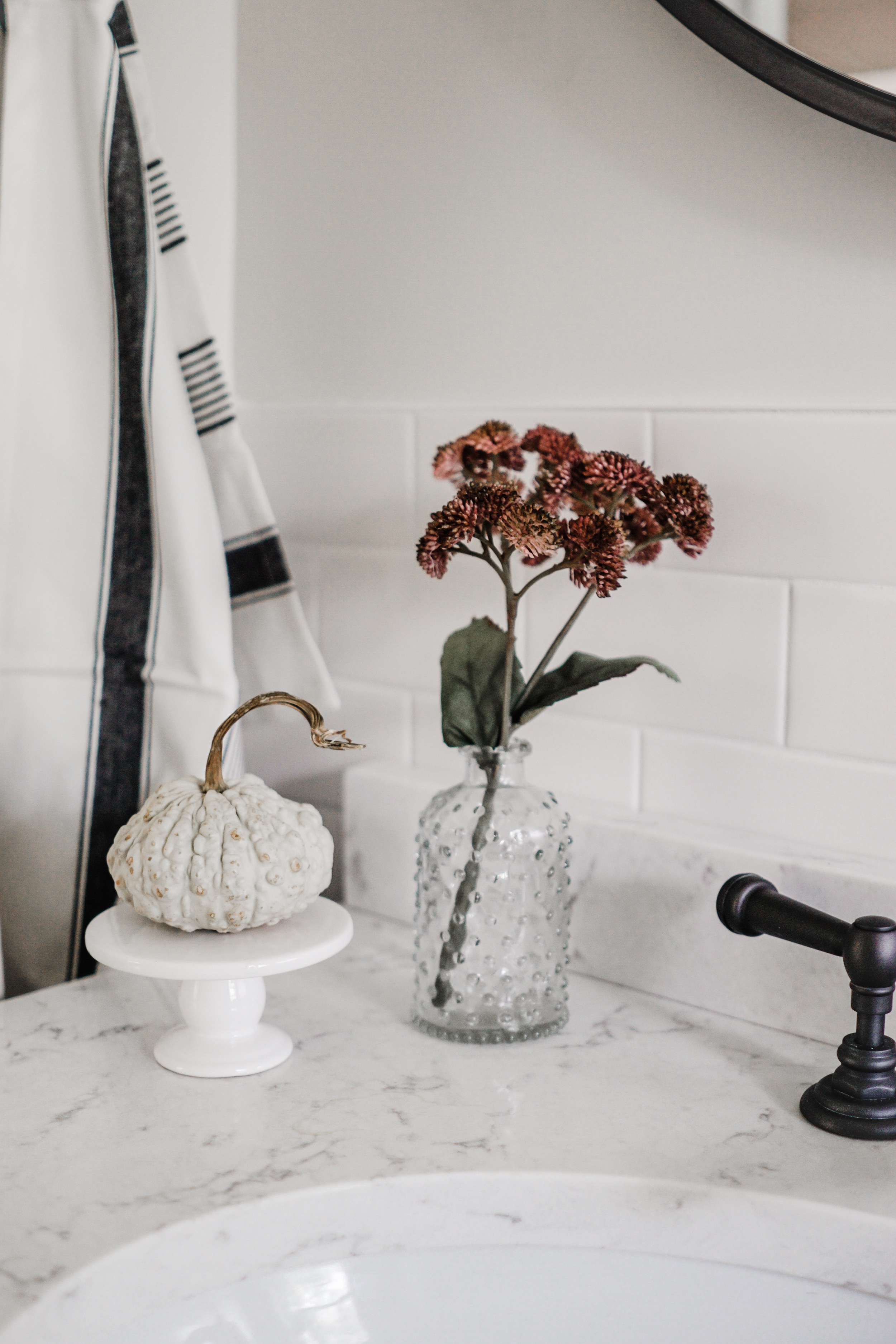 fall decor inspiration - add faux floral for a lil pop of color plus a pumpkin pedestal for fall vibes // fall bathroom decor idea