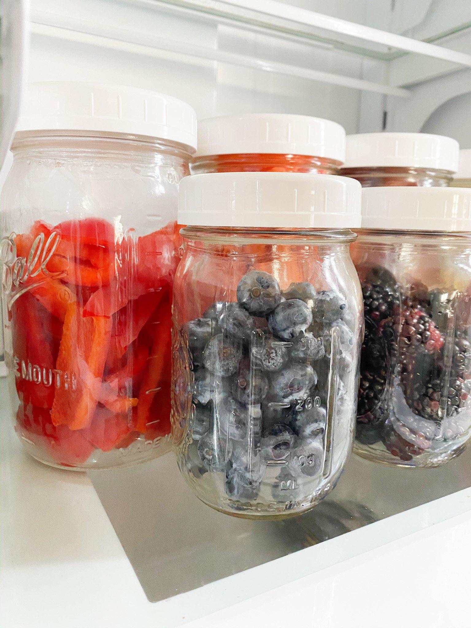 fresh blueberries stored in mason jars in the fridge