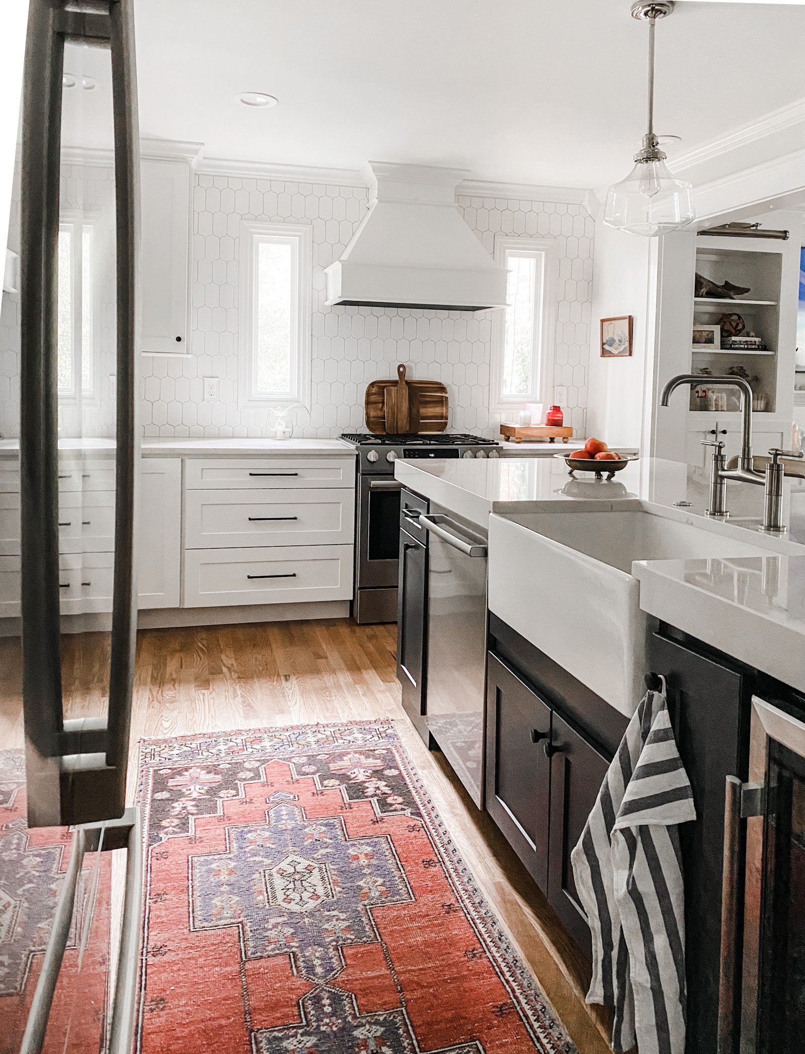 family-friendly kitchen with navy island and white cabinets