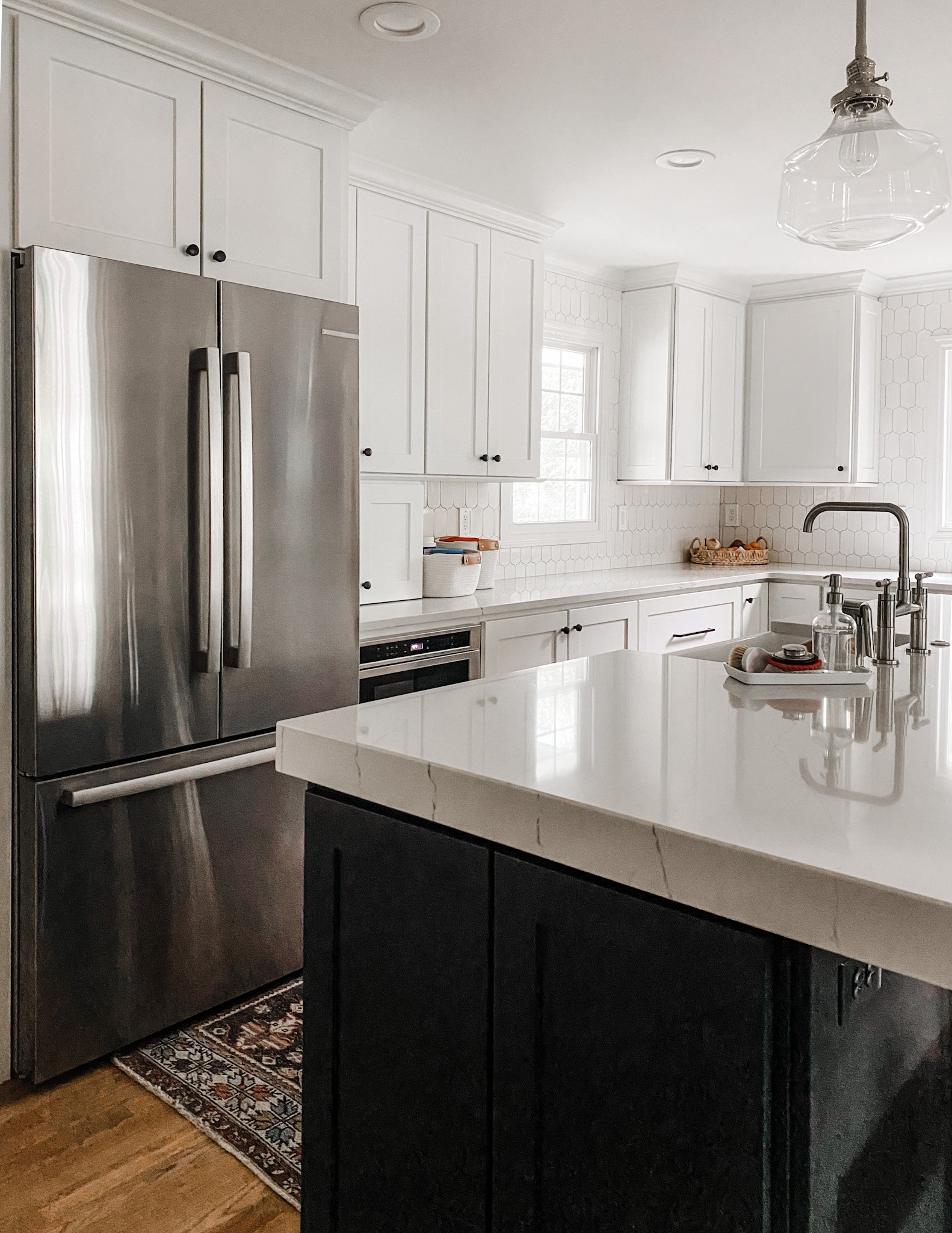 crisp white cabinets and a dark navy island in the kitchen